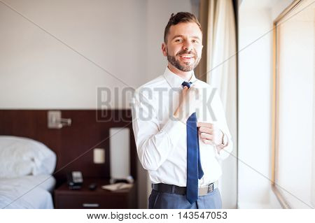 Latin Businessman Fixing His Tie In A Hotel