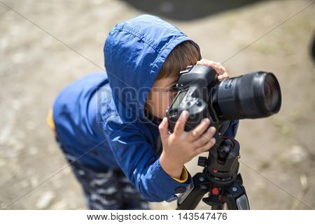 Small kid in a blue windcheater is making a photo shoot on the blurry background outdoors. He is looking into the viewfinder of the camera which is on the tripod. Horizontal.