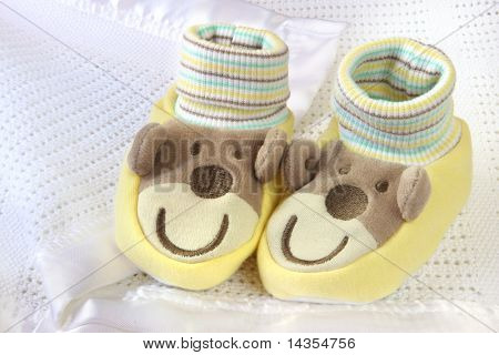 Cute baby booties with smiling monkey faces and ears.