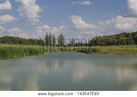 beautiful landscape with the lake and clouds in a sunny weather