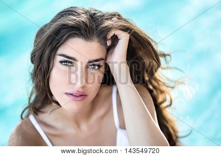 Amazing girl in a white swimsuit looks into the camera with parted lips on the background of the swimming pool. She holds her left hand on the head. Outdoors. Horizontal.