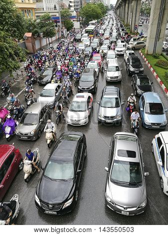 Hanoi, Vietnam - Aug 22, 2016: Many cars and motorbikes are stuck in a traffic jam on rush hour with noise and smoke  in Hanoi capital city.