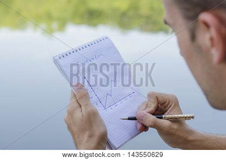 the young guy writes down in a notebook outdoors