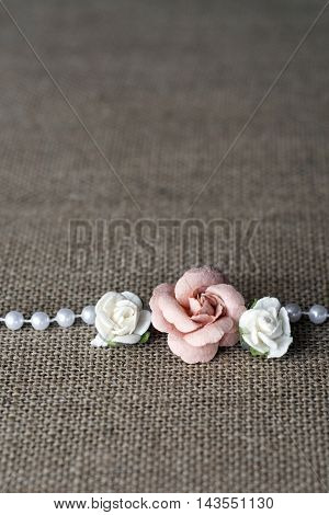 pink and white rose with pearls on burlap background