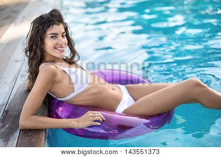 Smiling girl in a white swimsuit on the purple rubber ring in the swimming pool looks into the camera. She holds her elbows on the pool's floor. Outdoors. Horizontal.