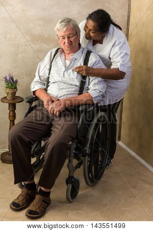 Grumpy old grandpa in nursing home receiving medication by a nurse