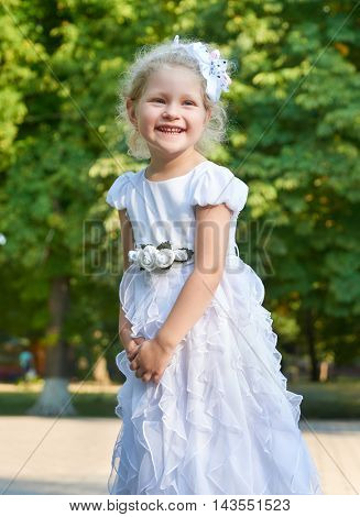 child girl portrait, posing in white gown, happy childhood concept, summer season in city park