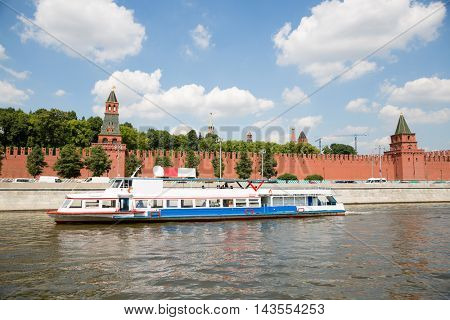 Excursion ship goes along the Moscow River near the walls of the Moscow Kremlin