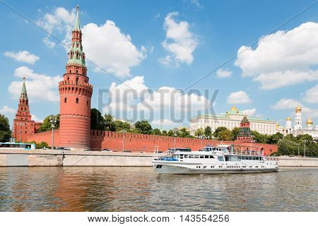 Passenger excursion boat goes across Moscow river in Moscow Kremlin