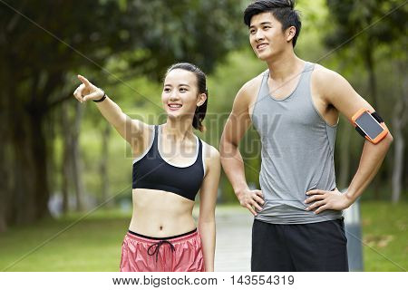 young asian couple exercising in park woman pointing at something in the distance.