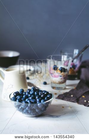 Healthy breakfast parfait with homemade granola, yogurt and blueberries on a marble table. Toned image. Food still life