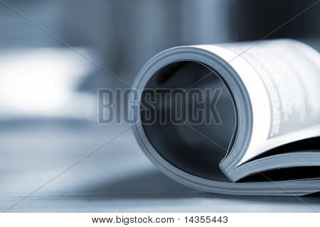 Rolled glossy magazine on a table, with coffee cup behind.  Very shallow depth of field, blue tone.