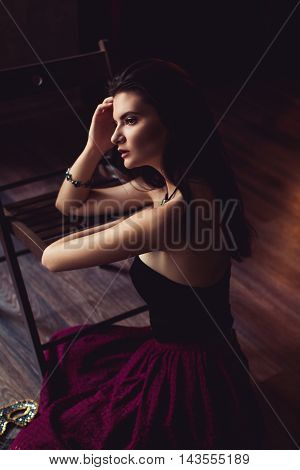 young brunette model woman posing in fashionable clothes in burlesque fitting room