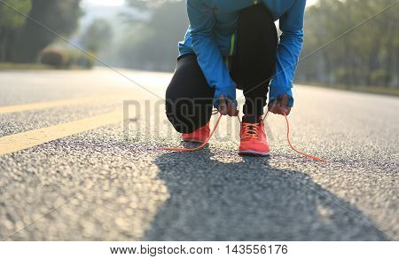young woman runner tying shoelaces on road