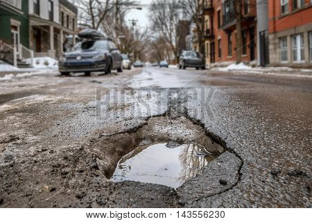Large deep pothole in Montreal street Canada.
