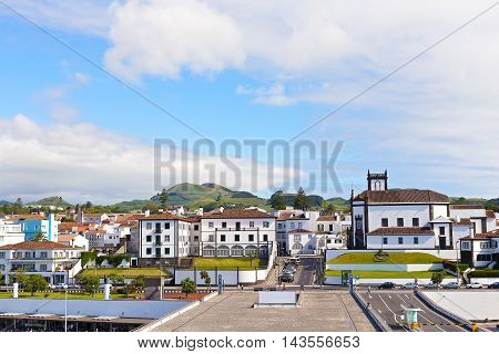View on Ponta Delgada from the ocean pier Azores Portugal. White houses with colorful tiled roofs and countryside with mountain ridge on the horizon.
