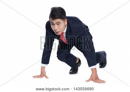 Isolated young businessman kneeling as if about to start a race