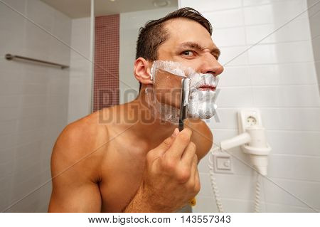 Man shaving razor. Unhappy man shaved half of his face.