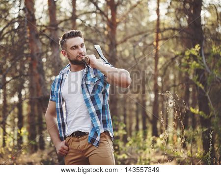 Lumberjack holding an ax on his shoulder. Woodcutter in plaid shirt chooses a tree. Felling trees. Logging. Manual labor.