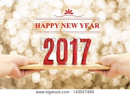 Hand holding wood plate with 2017 Happy new year red glitter number at blur golden sparkling bokeh light (,3d rendering text) backgroundHoliday concept .