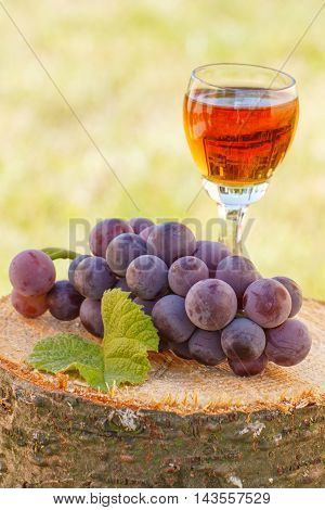 Grapes With Leaf And Glass Of Wine On Wooden Stump In Garden
