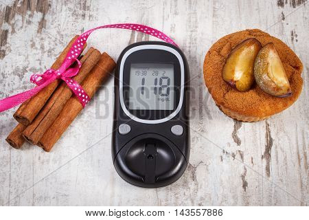 Glucometer, Muffins With Plums And Cinnamon Sticks On Wooden Background, Diabetes And Delicious Dess