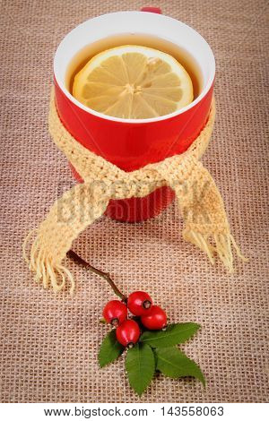 Cup Of Tea With Lemon Wrapped Woolen Scarf And Autumn Decoration