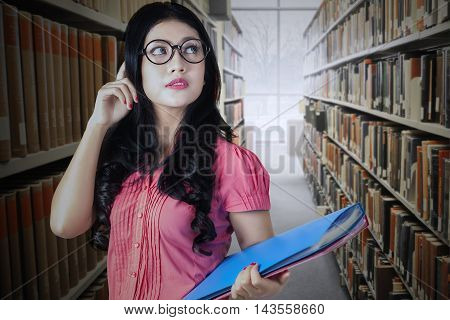Photo of a beautiful college student standing in the library aisle while wearing glasses and holding a folder