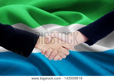 Photo of a business handshake with two worker hands closing a deal by shaking hands in front of a national flag of Sierra Leone
