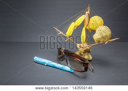Composition With Ship, Seashells, Pen And Glasses On Black Background