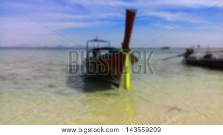 Small boat washed up on shore bright blue sky in background. blur picture.