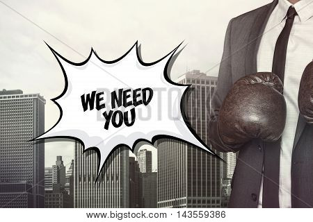 We need you text on speech bubble with businessman wearing boxing gloves