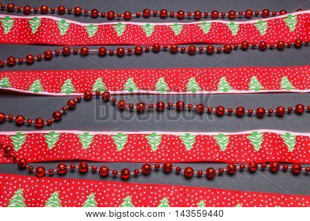 Christmas Decorations, Red Beads And Tape With Fir On Black Background