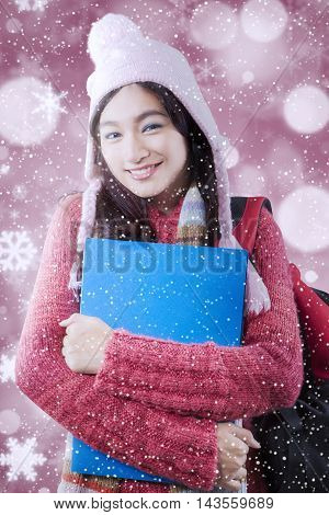 Portrait of a beautiful high school student wearing sweater and smiling at the camera with snowfall and blurred lights background