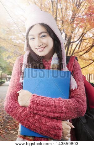 Cute high school student carrying bag and folder while smiling and wearing sweater at autumn park