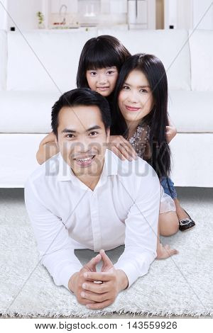 Happy Asian family smiling at the camera while lying down on the floor at home