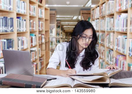 Photo of a clever learner sitting in the library while learning and doing school assignment