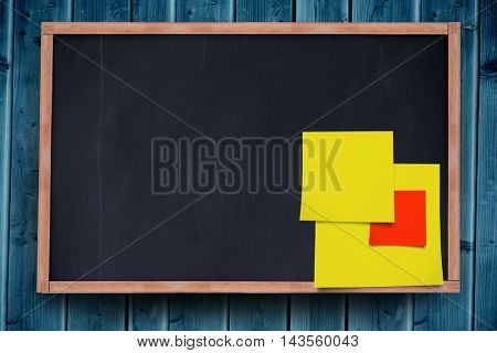 Blue adhesive note against blackboard with copy space on wooden board