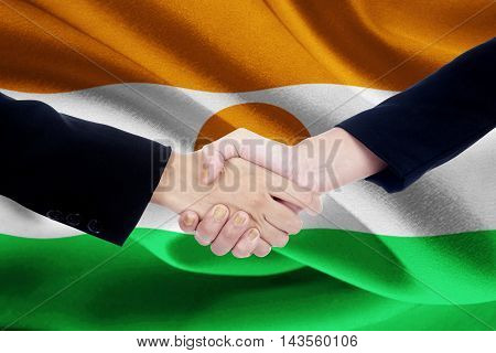 Image of a friendship handshake with two worker hands shaking hands with Niger flag