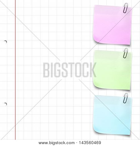 Purple adhesive note with paper clip against spiral notepad