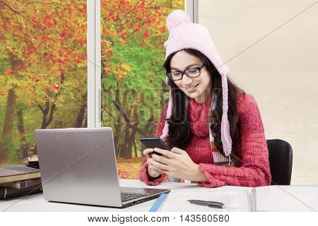 Female learner studying at home while wearing sweater and using mobile phone with autumn background on the window