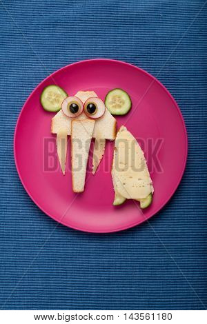 Funny sandwich elephant made on plate and fabric background