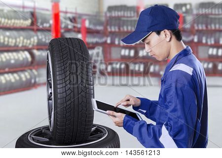 Photo of a male mechanic using a digital tablet while checking tires in the workshop