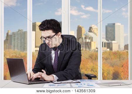 Photo of young businessman wearing formalwear working with laptop in the office near the window