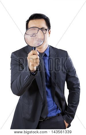 Male entrepreneur looking at the camera through a magnifying glass in the studio isolated on white background