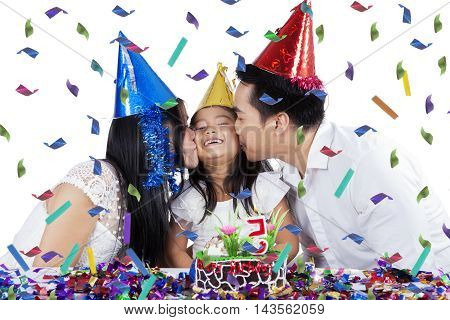 Two young parents kissing their daughter while celebrating her birthday party