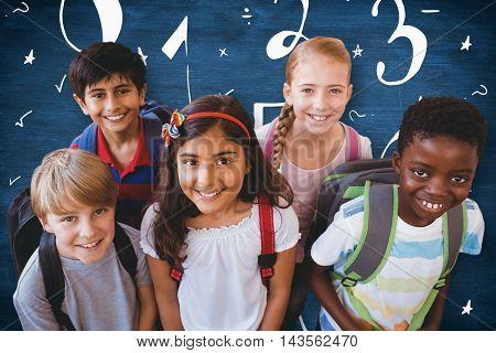 Smiling little school kids in school corridor against blue chalkboard