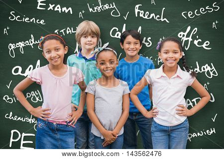 Cute pupils smiling at camera in classroom against green chalkboard