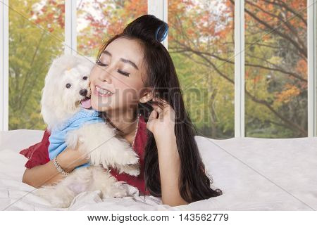 Portrait of a young pretty woman and her puppy lying on the bed at home with autumn background on the window