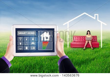 Hands holding a digital tablet with smart house controller applications shot with woman using laptop on the couch at field